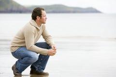 Uomo che si accovaccia sulla spiaggia Fotografia Stock Libera da Diritti