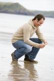 Uomo che si accovaccia sulla spiaggia Immagini Stock