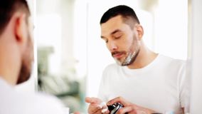 Uomo che si applica radendo schiuma alla barba al bagno video d archivio