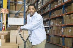 Uomo che si appoggia carrello in magazzino Fotografia Stock Libera da Diritti