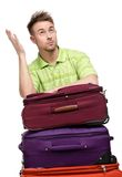 Uomo che si appoggia il mucchio delle valigie di viaggio Immagini Stock
