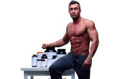 Uomo che si appoggia la tavola con nutrizione di sport Fotografie Stock Libere da Diritti