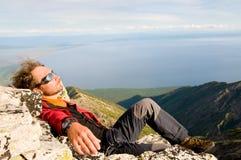 Uomo che si distende alla parte superiore della montagna Fotografia Stock Libera da Diritti