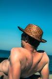 Uomo che si distende sulla spiaggia Fotografia Stock