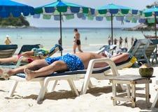 Uomo che si distende sulla spiaggia Immagini Stock Libere da Diritti