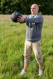 Uomo che si esercita con 3 chili di palla medica all'aperto Immagini Stock Libere da Diritti