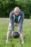 Uomo che si esercita con 3 chili di palla medica all'aperto Fotografie Stock