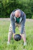 Uomo che si esercita con 3 chili di palla medica all'aperto Immagini Stock