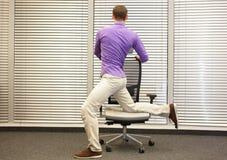 Uomo che si esercita sulla sedia in ufficio fotografia stock libera da diritti