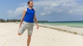 Uomo che si esercita sulla spiaggia. Sta allungando. Immagini Stock