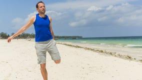 Uomo che si esercita sulla spiaggia. Sta allungando. Immagine Stock Libera da Diritti