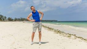 Uomo che si esercita sulla spiaggia. Sta allungando. Fotografia Stock