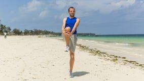 Uomo che si esercita sulla spiaggia. Sta allungando. Immagini Stock Libere da Diritti