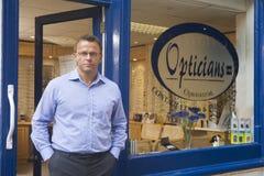 Uomo che si leva in piedi all'entrata di fronte degli optometristi immagini stock libere da diritti