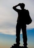 Uomo che si leva in piedi in cima ad una roccia Fotografia Stock