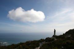 Uomo che si leva in piedi in cima alla montagna della Tabella Immagine Stock
