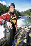 Uomo che si leva in piedi con la zattera al lato del fiume Fotografie Stock