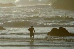 Uomo che si leva in piedi lungo la linea costiera Immagini Stock Libere da Diritti
