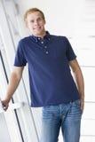 Uomo che si leva in piedi nel sorridere del corridoio Immagini Stock