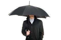 Uomo che si leva in piedi sotto un ombrello. Fotografia Stock