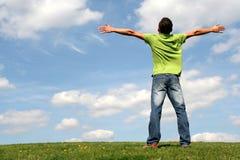 Uomo che si leva in piedi sull'erba Immagini Stock