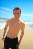 Uomo che si leva in piedi sulla spiaggia esotica fotografia stock libera da diritti