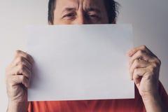 Uomo che si nasconde dietro il Libro Bianco in bianco Immagine Stock