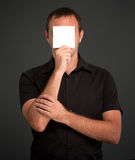 Uomo che si nasconde dietro una nota in bianco Fotografia Stock