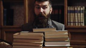 Uomo che si nasconde dietro una pila di libri Giovane pellame sorpreso dello studente dietro i libri impilati Ritratto alto vicin stock footage
