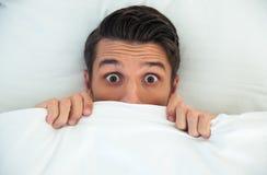 Uomo che si nasconde a letto sotto la coperta a Fotografia Stock