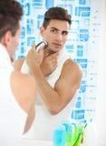 Uomo che si rade con il rasoio elettrico immagine stock