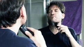 Uomo che si rade davanti al primo piano del movimento lento dello specchio video d archivio
