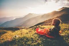Uomo che si rilassa in sacco a pelo che gode delle montagne di tramonto Fotografia Stock Libera da Diritti