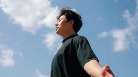 Uomo che si rilassa su una libert?, fondo del cielo blu, mani sollevate stock footage