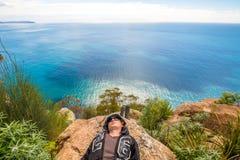Uomo che si rilassa su una scogliera Fotografia Stock