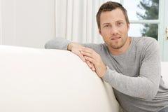 Uomo che si rilassa sul sofà a casa. Immagini Stock