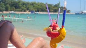 Uomo che si rilassa sulla spiaggia con il coctail della frutta archivi video