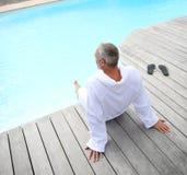 Uomo che si rilassa vicino alla piscina Fotografie Stock