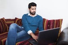 Uomo che si siede in abbigliamento casual che lavora al computer immagine stock libera da diritti