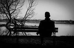 Uomo che si siede accanto al fiume Fotografie Stock Libere da Diritti