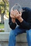 Uomo che si siede al gravesite Immagine Stock