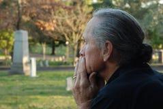Uomo che si siede al gravesite Fotografie Stock