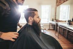Uomo che si siede al salone di capelli Fotografia Stock Libera da Diritti