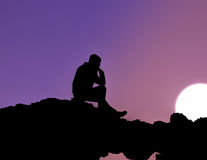 Uomo che si siede al tramonto Immagini Stock