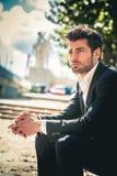 Uomo che si siede all'aperto nella città sulla via immagini stock libere da diritti