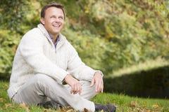 Uomo che si siede all'esterno nel paesaggio di autunno Fotografia Stock