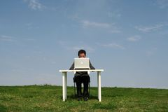 Uomo che si siede allo scrittorio, all'aperto Fotografia Stock