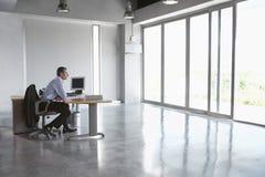 Uomo che si siede allo scrittorio in ufficio vuoto Fotografia Stock Libera da Diritti