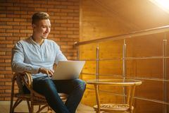 Uomo che si siede a casa e che lavora al computer portatile maschio che lavora dal Ministero degli Interni del sottotetto Fotografia Stock Libera da Diritti