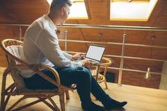 Uomo che si siede a casa e che lavora al computer portatile maschio che lavora dal Ministero degli Interni del sottotetto Immagine Stock